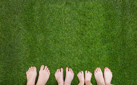 Happy people feet standing on cool grass