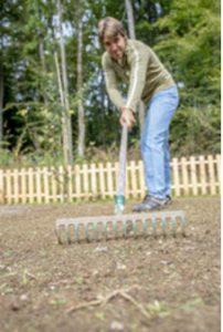 Man raking dirt in preparation for new sod.